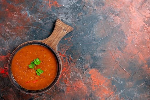 混合色のテーブルの右側にある茶色のまな板にクラシックなトマトスープ