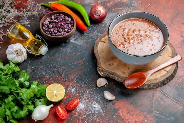 Classica zuppa di pomodoro con cibi e fagioli, bottiglia di olio e un mazzo di pomodoro verde limone su tavola di colori misti