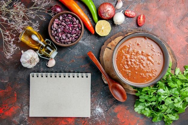 Classica zuppa di pomodoro con cibi e fagioli, bottiglia di olio e un mazzo di pomodoro verde limone e taccuino sulla tavola di colori misti