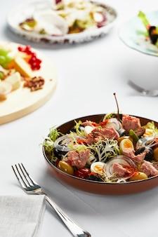 Классический салат из тунца нисуаз с яйцом, картофелем, помидорами, анчоусами, луком и оливками, соусом винегрет, авторская подача нисуаз.
