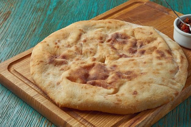 古典的なトルコのパンのフラットブレッドは、緑のテーブルの上の木の板で提供されます。トルコのパン Premium写真