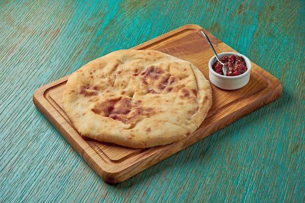 古典的なトルコのパンのフラットブレッドは、緑のテーブルの上の木の板で提供されます。トルコのパン