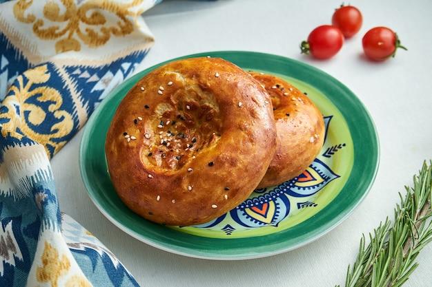Классическая турецкая лепешка из хлеба с кунжутом в узорной тарелке на белой скатерти