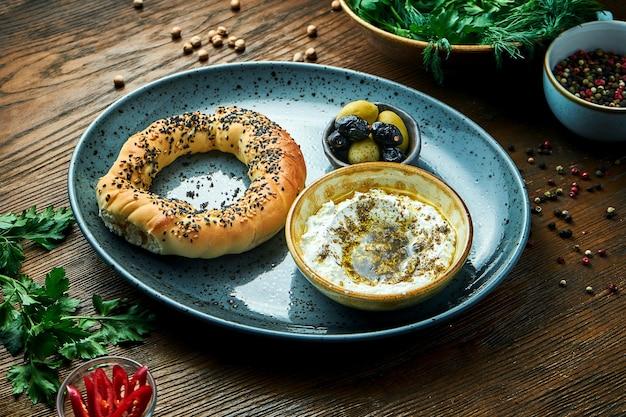 クラシックなトルコ式朝食-オリーブオイルとスパイスを添えたフェタチーズのムースを添えたシミットを、オリーブと一緒に青いプレートでお召し上がりいただけます。木製のテーブル。レストランの食べ物。シミット-ケシの実またはゴマの入ったベーグル