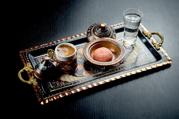 Classic turkish coffee, made in the sand, served on a national tray with ornaments, biscuits and water. dark table
