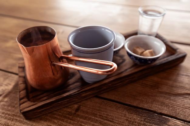 정통 터키식 커피. 나무 쟁반, 커피 컵, 초콜릿, 쿠키, 구리 터크가 나무 테이블에 있습니다.