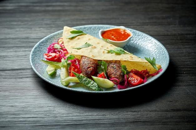 Классическое турецкое блюдо - люля-кебаб на гриле в лаваше со свежими овощами. выборочный фокус