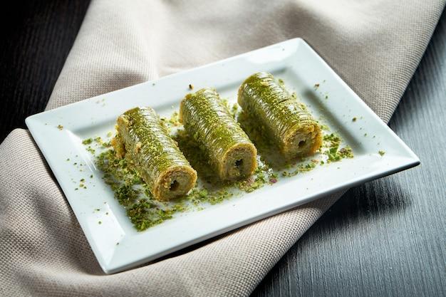 古典的なトルコのスイーツ-白いプレートにパフペストリーからの蜂蜜とピスタチオを添えたバクラヴァ。クローズアップ、セレクティブフォーカス