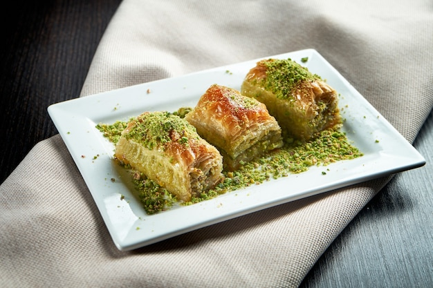 Classic turkish sweets - baklava with honey and pistachios from puff pastry in a white plate. close up, selective focus