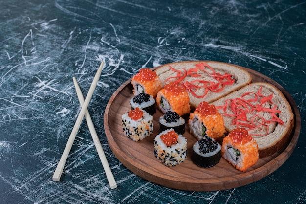Классические два вида суши на деревянной доске с палочками для еды и ломтиками хлеба.