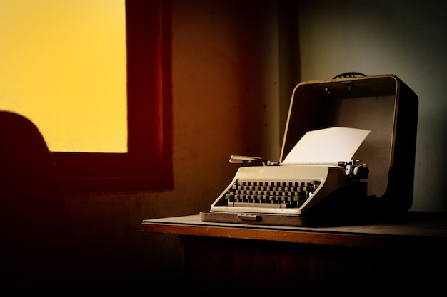 The classic typewriter on desk in dusty room.