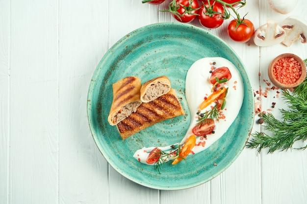 Классические украинские блины (блинчики) с начинкой из мяса на голубой тарелке со сметаной на белом деревянном столе.