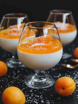 Classic vanilla panna cotta in a glass with apricots and coconut flakes