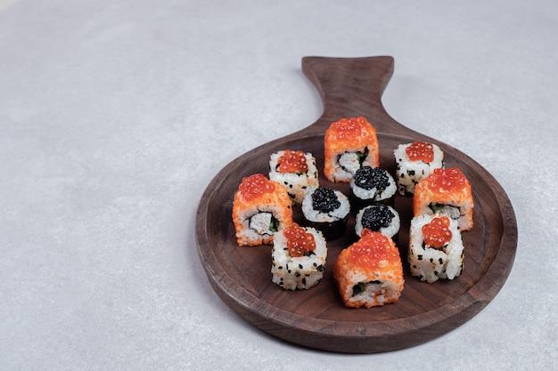 箸で木の板に巻いた定番の巻き寿司。