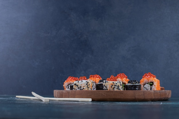 Classic variety of sushi rolls on wooden board with chopsticks.