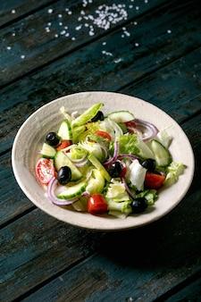 白いセラミックプレートにトマト、キュウリ、タマネギ、サラダの葉、ブラックオリーブを添えたクラシックな野菜サラダ。暗い木製のテーブル。