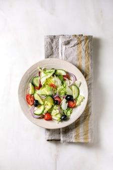 トマト、キュウリ、タマネギ、サラダの葉、ブラックオリーブを布ナプキンに白いセラミックプレートで添えたクラシックな野菜サラダ。白い大理石の背景。フラットレイ、コピースペース