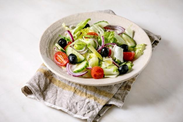 トマト、キュウリ、タマネギ、サラダの葉、ブラックオリーブを布ナプキンに白いセラミックプレートで添えたクラシックな野菜サラダ。白い大理石の背景。