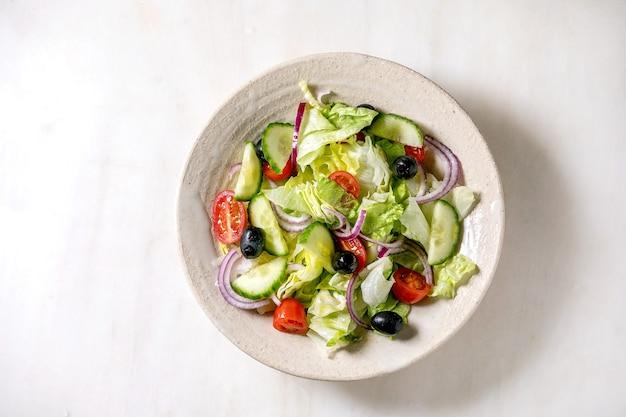白いセラミックプレートにトマト、キュウリ、タマネギ、サラダの葉、ブラックオリーブを添えたクラシックな野菜サラダ。白い大理石の背景。フラットレイ、コピースペース