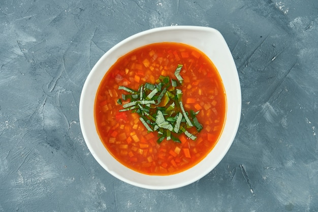 Classic vegetarian vegetable minestrone soup in a white bowl on a concrete surface. top view