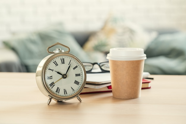 Classic vintage  alarm clock and  coffee cup on wooden background