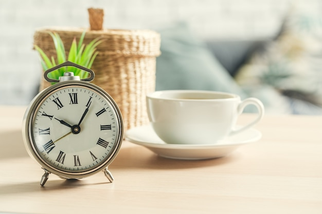 Classic vintage  alarm clock and  coffee cup on wooden