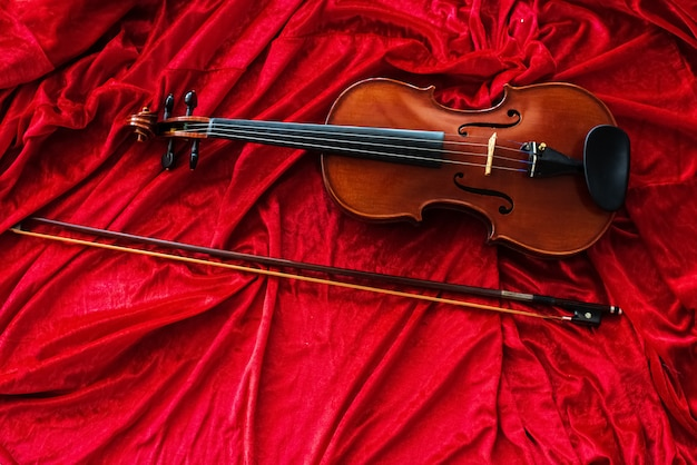 The classic violin and bow put on red cloth background,show detail of the instrument