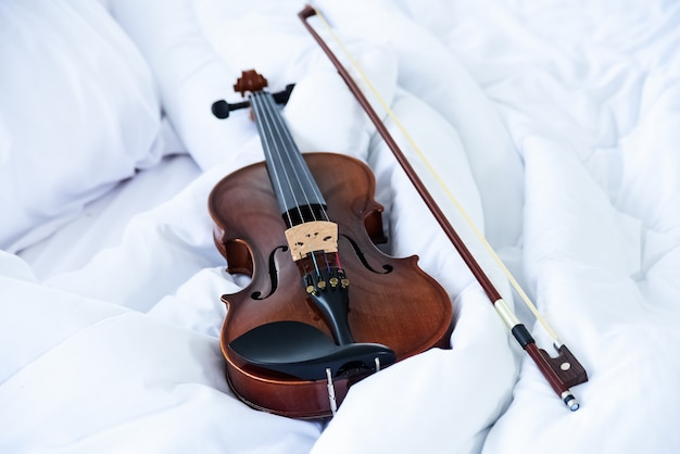 The classic violin and bow put on white blanket, show detail of stringed instrument, blurry light around