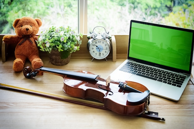 The classic violin and bow put on wooden desk, beside laptop and alarm clock.