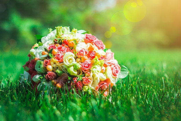 장미, 유스토마, 프리지아로 만든 클래식 웨딩 부케는 울창한 풀밭에 있습니다. 밝은 녹색과 에메랄드빛 여름 사진. 결혼식 세부 사항입니다.