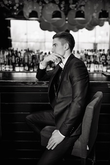 Classic wedding photo. portrait of a groom sitting on a chair by the bar. low key.