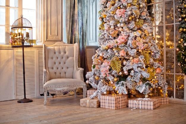 古典的な白いクリスマスのインテリア。プレゼントと点滅する花輪で飾られたクリスマスツリー
