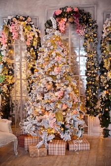 클래식 화이트 크리스마스 인테리어. 선물과 번쩍이는 화환으로 장식 된 눈이 내리는 나무