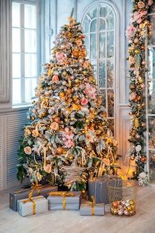 古典的な白いクリスマスのインテリア。プレゼントと点滅する花輪で飾られた雪に覆われた木