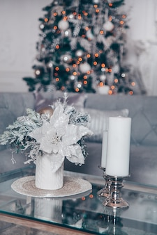 Classic white christmas interior with modern elements and new year tree decorated.