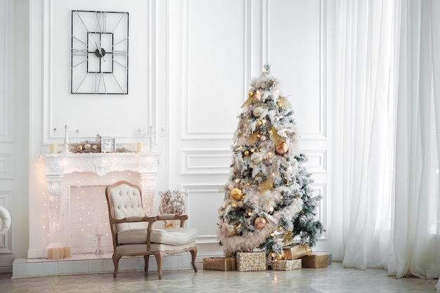 Classic white christmas interior with tree decorated. fireplace with grey chair, clocks on the wall and presents under the tree
