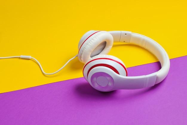 Классические белые наушники на фиолетовом фоне желтой бумаги. ретро стиль. поп-культура 80-х.