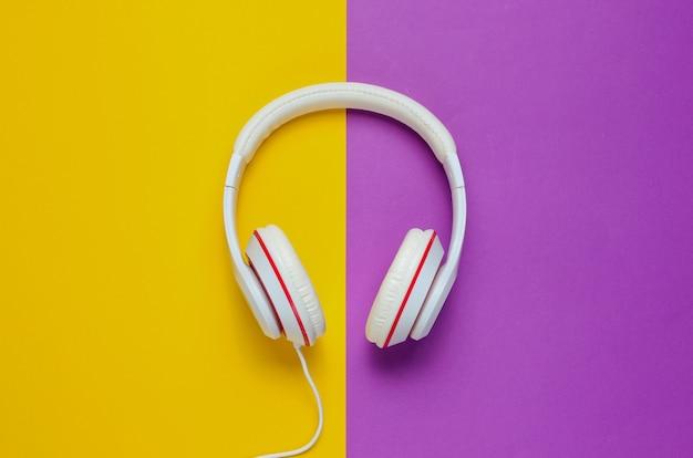 Классические белые наушники на фиолетовом фоне желтой бумаги. ретро стиль. популярная культура. минимальная музыкальная концепция