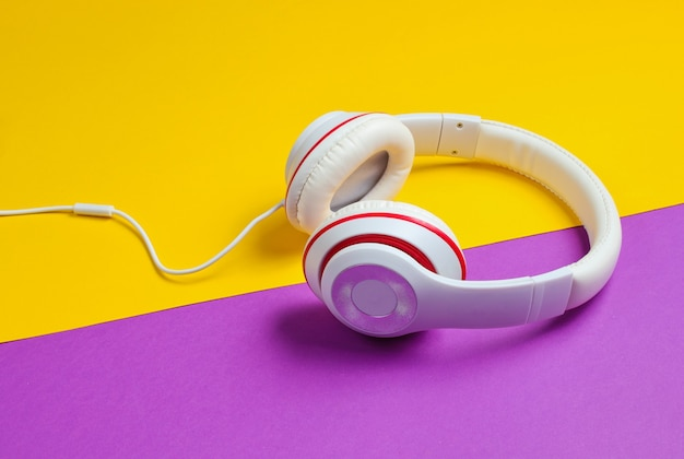 Classic white headphones on purple yellow paper background. retro style. 80s pop culture.