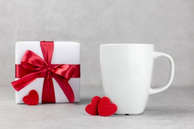 밝은 회색 콘크리트 표면에 빨간 하트와 선물 상자가있는 고전적인 흰색 머그잔 모형