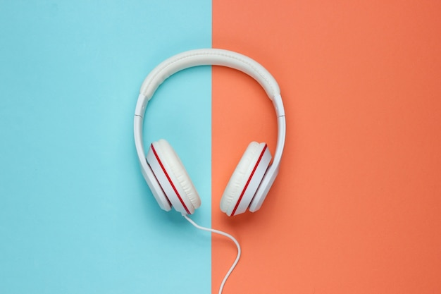 Classic white wired headphones on colored paper background. retro style. 80s. pop culture. top view. minimal music concept