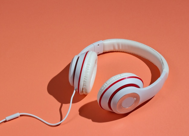 Classic white wired headphones on coral paper background. retro style. 80s. pop culture. minimal music concept