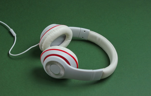 Classic white wired headphones on green paper background. retro style. 80s. pop culture. music lover