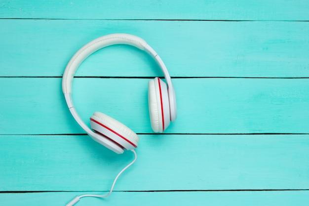 青い木製の背景にクラシックな白い有線ヘッドフォン。レトロなスタイル。 80年代。ポップカルチャー。上面図。ミニマルミュージックのコンセプト