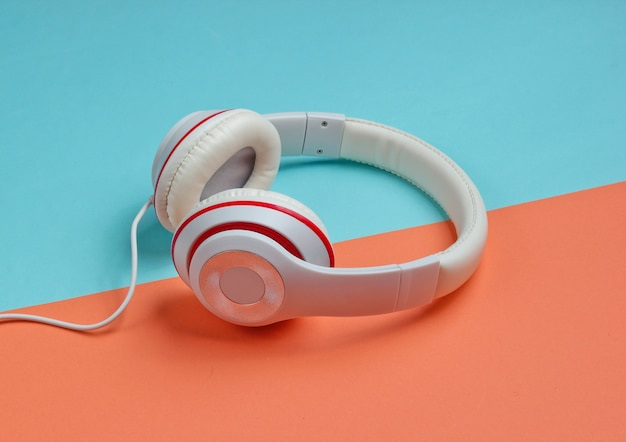 色紙の背景に古典的な白い有線ヘッドフォン。レトロなスタイル。 80年代。ポップカルチャー。ミニマルミュージックのコンセプト