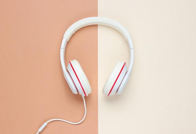 色紙の背景に古典的な白い有線ヘッドフォン。レトロなスタイル。 80年代。ポップカルチャー。上面図。ミニマルミュージックのコンセプト