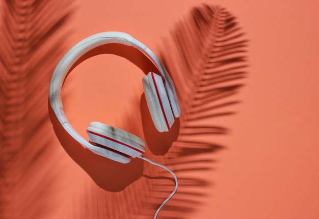 Классические белые проводные наушники на фоне коралловой бумаги с тенью пальмовых листьев. ретро стиль. 80-е гг. популярная культура. минимальная музыкальная концепция