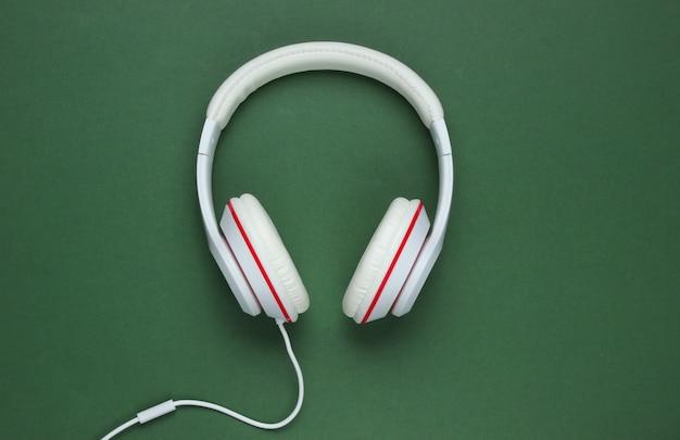 緑の紙の背景に古典的な白い有線ヘッドフォン。レトロなスタイル。 80年代。ポップカルチャー。上面図。音楽愛好家