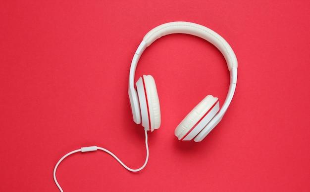 赤い紙の背景に古典的な白い有線ヘッドフォン。レトロなスタイル。 80年代。ポップカルチャー。音楽愛好家。上面図