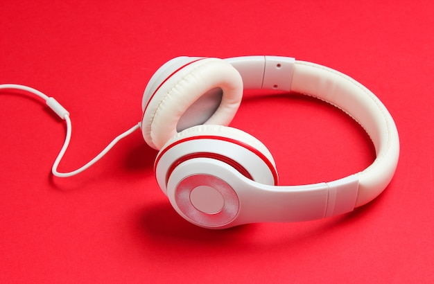 赤い紙の背景に古典的な白い有線ヘッドフォン。レトロなスタイル。 80年代。ポップカルチャー。音楽愛好家